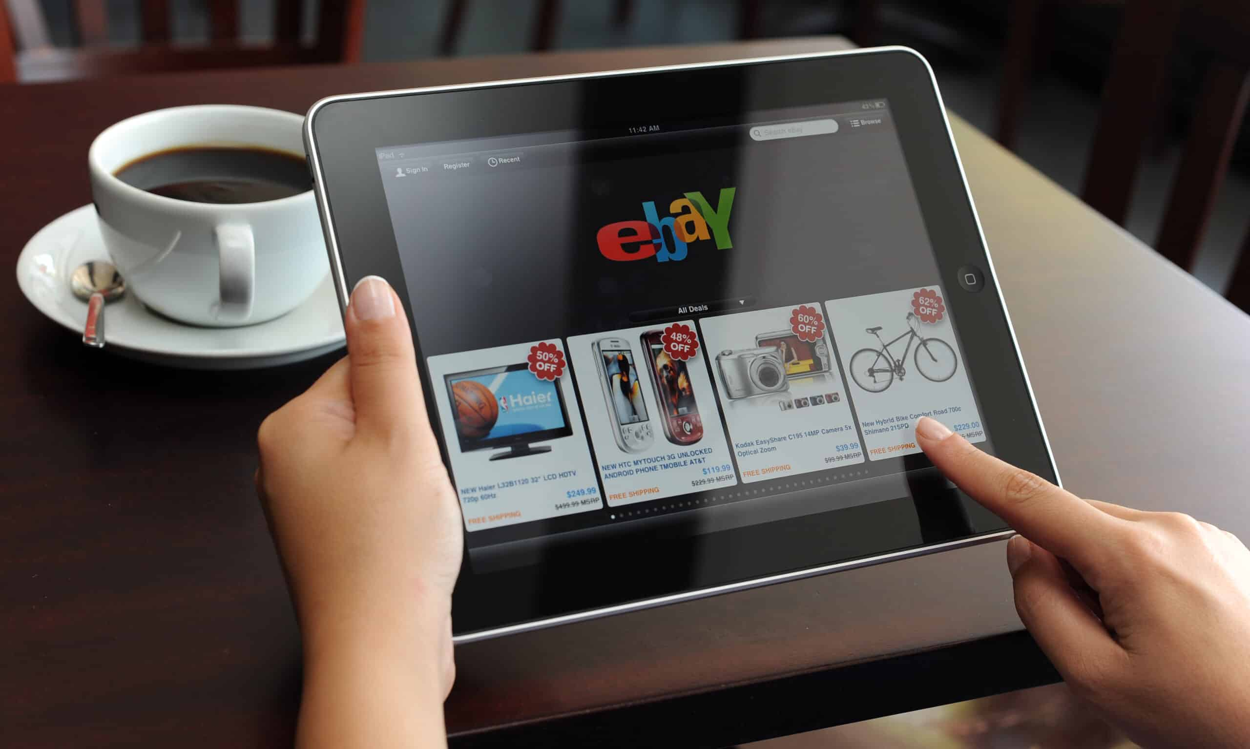 d holding iPad displaying eBay application. eBay seller update autumn 2021 came out in early Septermber