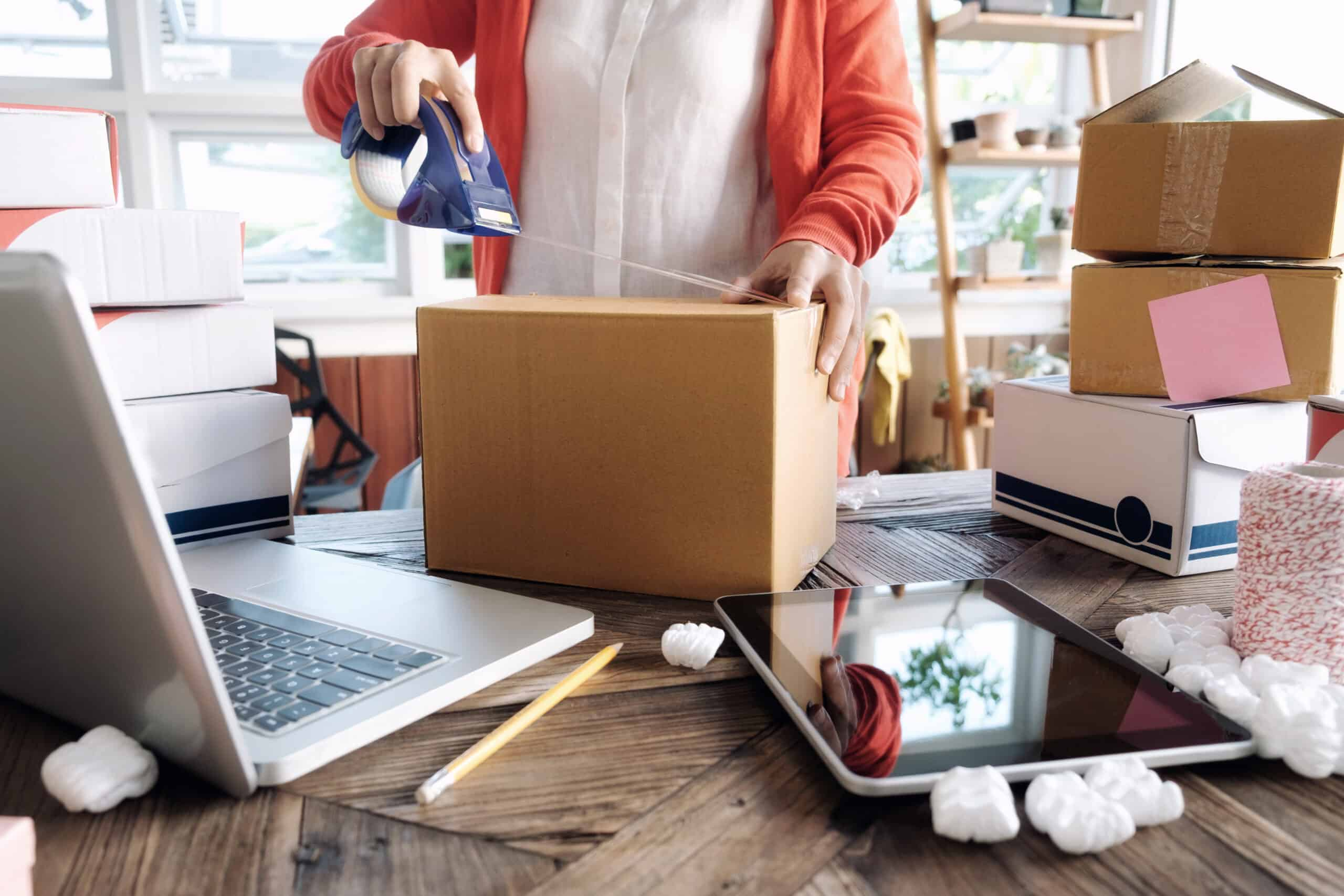 Young startup entrepreneur small business owner working at home, packaging and delivering items for Amazon FBA in preparation for Black Friday