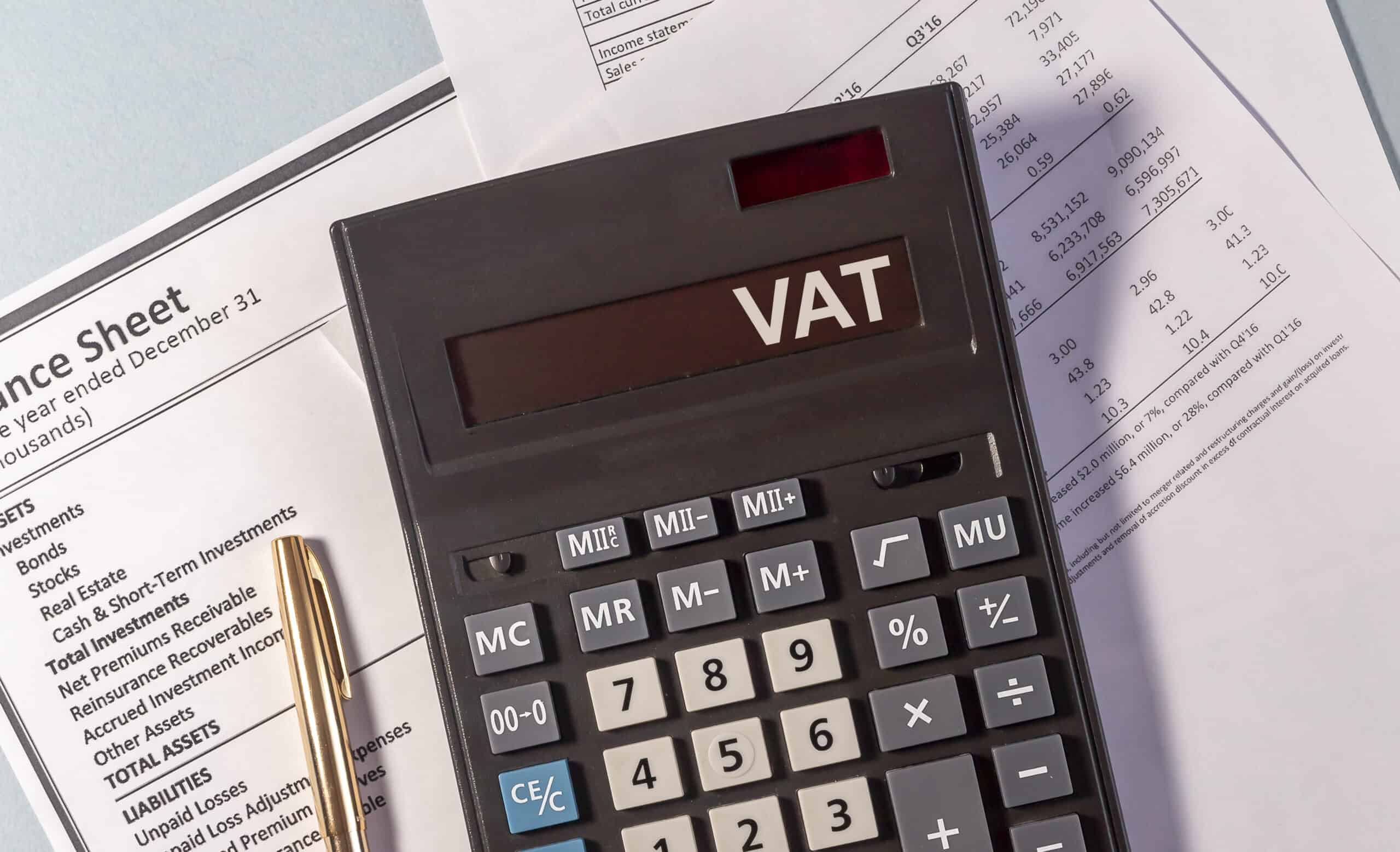 VAT word on display of calculator on postponed import vat accounting papers documents and golden pen